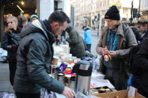 Simply Waste Solutions driver, Cledywn, pouring hot drinks for homeless people as he helps Street Angels UK
