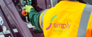 Simply Waste Solutions driver in high visibility jacket pressing bin lift button on truck