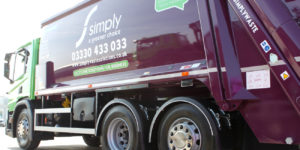 Simply Waste Solutions trade waste truck, sunlight beaming off purple
