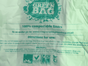 Compostable green bag with compostable recycling symbol