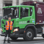 Small image of truck driver next to 19 plate Simply Waste Solutions trade waste truck