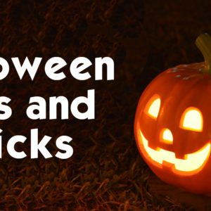 Halloween recycling tips and tricks text next to candle lit, carved pumpkin on field of grass