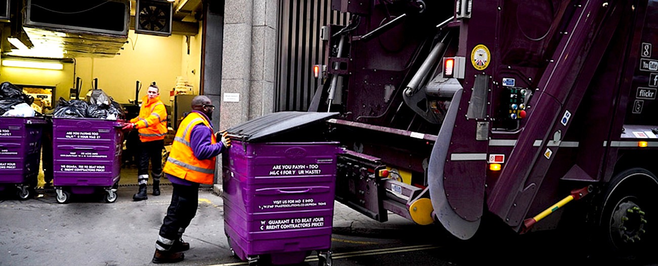 Simply Waste Solutions driver pushing wheelie bin up to trade waste truck ready to be tipped