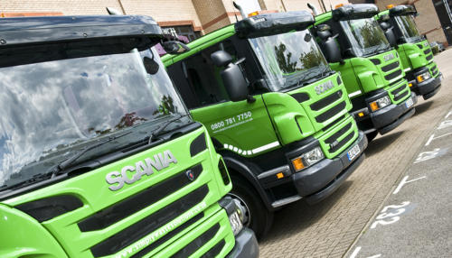 Row of Simply Waste Solutions 12 plate trade waste trucks