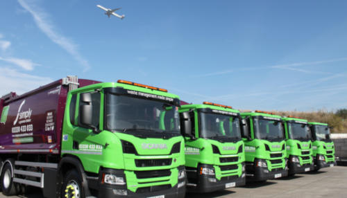 Plane flying over Simply Waste Solutions trucks near Heathrow